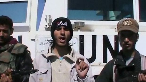 A member of the Al Yarmouk Martyr brigade makes a statement in front of a white vehicle with 'UN' written on it at what ...