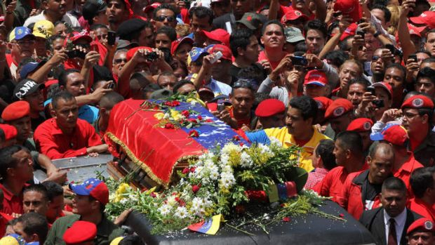 Venezuela's Vice President Nicolas Maduro, wearing a yellow jacket, walks alongside the flag-draped coffin carrying the ...