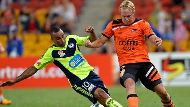 Archie Thompson shows his defensive skills, wresting the ball from Roar's Mitch Nichols in the drawn match at Suncorp ...