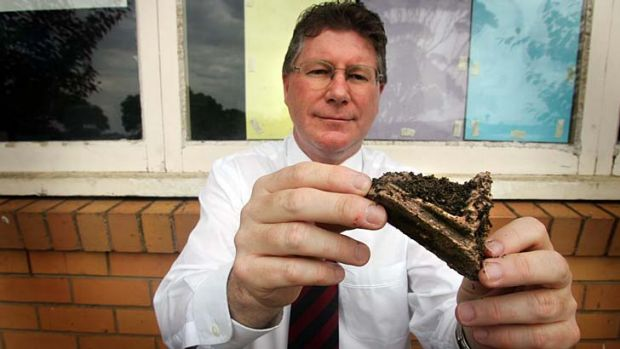 Denis Napthine shows a rotten piece of wood from a school's window pane in 2006.