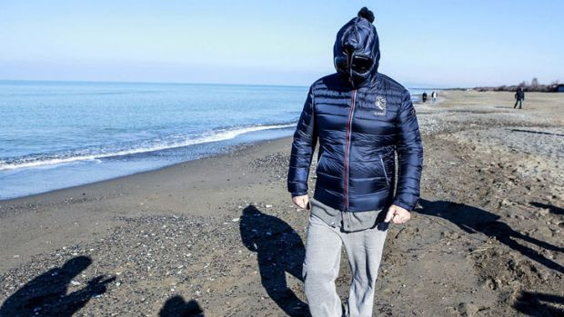 Comic-turned-political leader Beppe Grillo wears a mask as he walks along the beach in Marina di Bibbona, central, ...