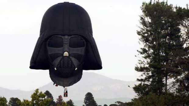 A hot air balloon shaped like Darth Vader's head lands after a sunrise flight in Canberra.