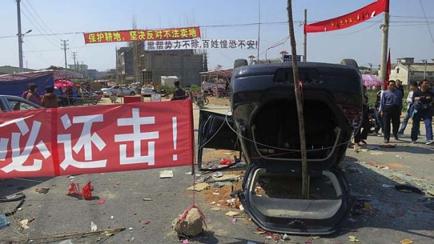 A sign proclaiming 'We must retaliate' is displayed next to an overturned car at the entrance of Shangpu village in ...