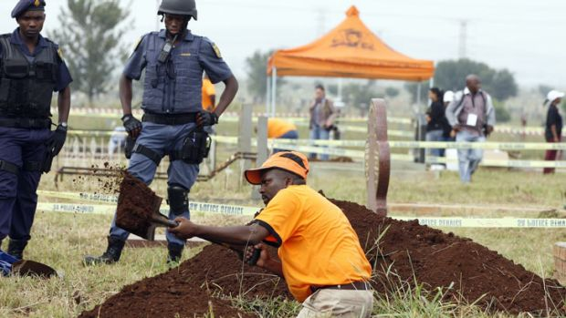 National Prosecuting Authority worker digs up a grave for exhumation of two bodies, that are believed be those of young ...