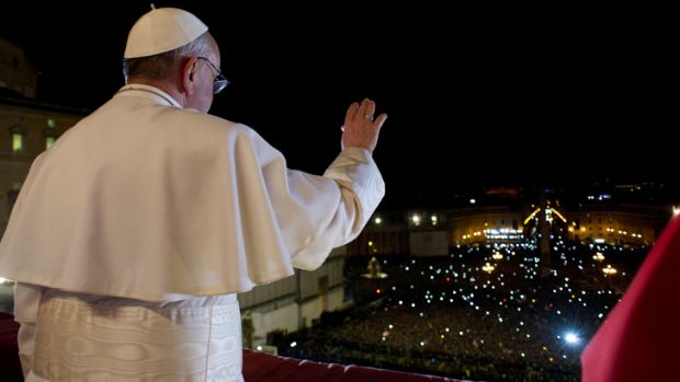 Pope Francis waves to the crowd from the central balcony of St. Peter's Basilica at the Vatican.