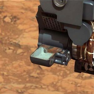 Futher evidence of conditions conducive to life: The Curiosity rover holds a scoop of powdered bedrock.