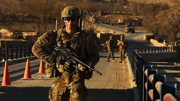 Vigilant: Australian soldiers patrol and search the Puza bridge in Oruzgan province for improvised explosive devices ...