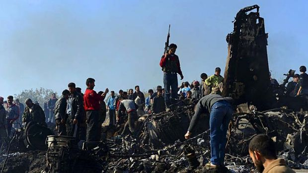 Syrian rebels and civilians gather around the remains of a Syrian government fighter jet.