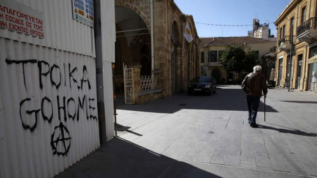A man walks past anti-austerity graffiti in the Cypriot capital of Nicosia at the weekend. The measures included in a ...