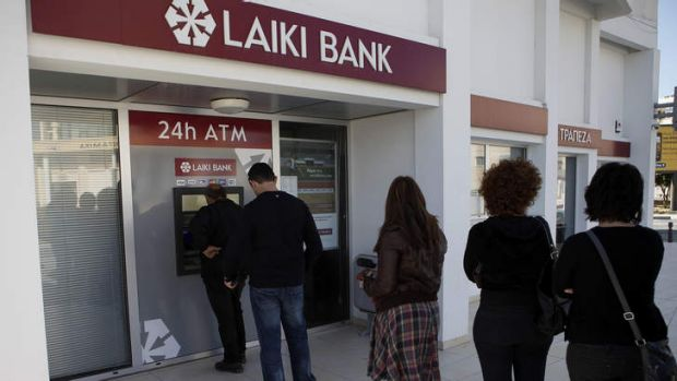 Rush for cash: Customers queue at a Laiki Bank ATM.