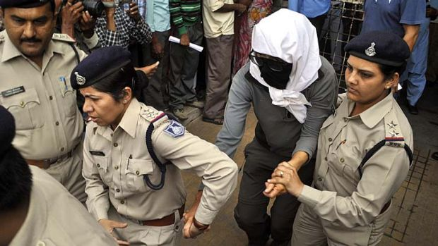 Traumatising: A Swiss woman is escorted by police for a medical examination at a hospital in Gwalior.