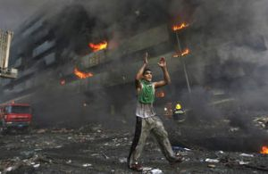 A man runs down a Baghdad street warning people to flee shortly after a twin car bomb attack at a market in 2007.