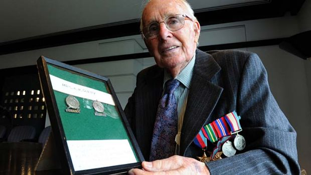 Fighting spirit: Bruce Guppy with the two badges his mother received.