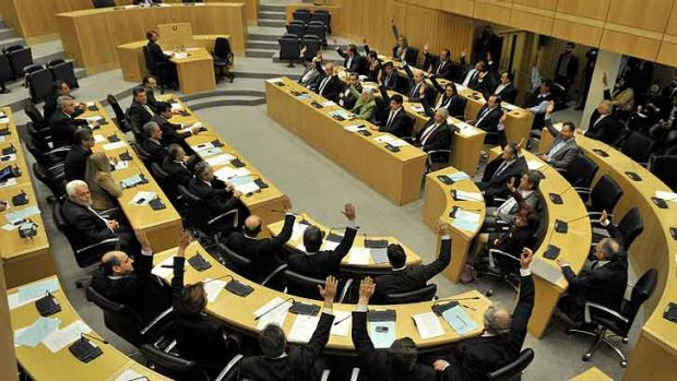 Rejected ... lawmakers raise their arms to vote against a controversial bill to tax deposits in Nicosia.