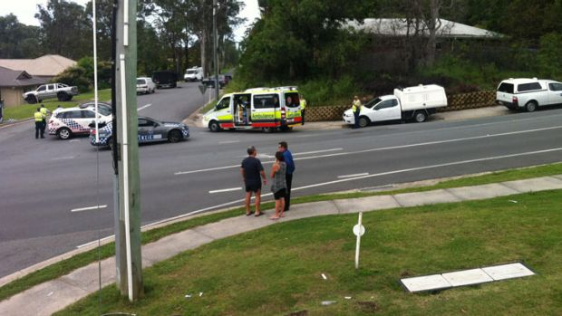 The father of the man (left) at the centre of a siege on the Gold Coast talks with his son's partner and police officers ...