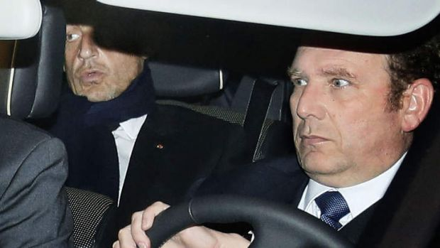Former French president Nicolas Sarkozy, left, leaves the courthouse in Bordeaux.