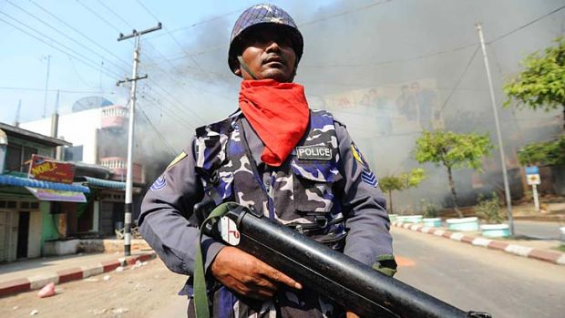Violent clashes: A policeman stands guard on a street in Meiktila.