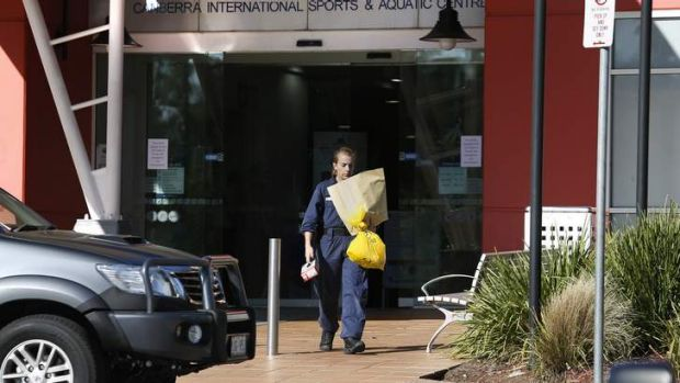 A forensic investigator carries items from the Canberra International Sports and Aquatics Centre in Belconnen after the ...