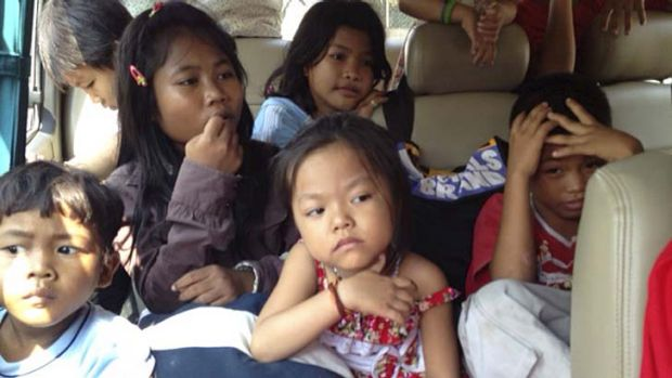 Children wait on a bus after being removed.