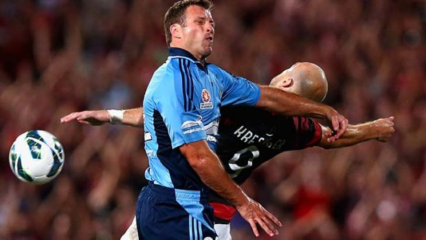 Excuse me mate: Sydney FC's Lucas Neill gets handsy mid-air with Wanderers counterpart Dino Kresinger.