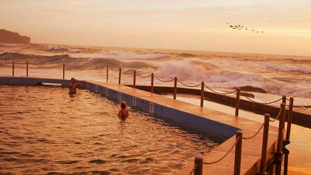 Early to rise: Swimmers watch the sun rise over the south Curl Curl rock pool. Sydney is set for another hot week, with ...