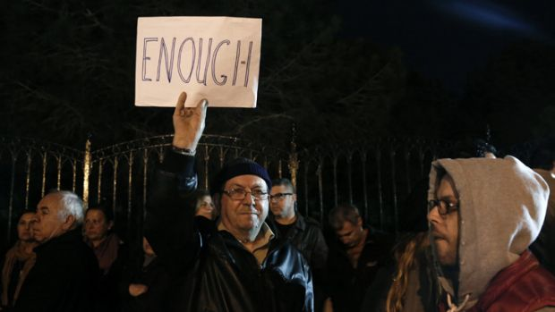 A protester raises a placard during an anti-bailout rally outside the presidential palace in Nicosia, Cyprus.