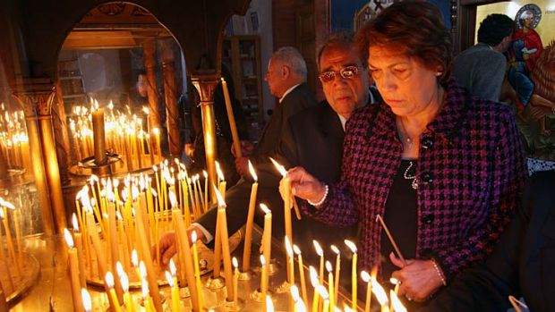 Praying for a fiscal lifejacket: Cypriots light candles during a Sunday service at Saint Mamas Orthodox church in ...