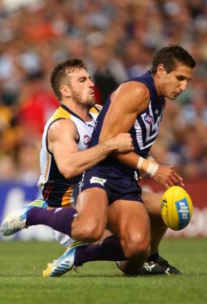Eric Mackenzie of the Eagles tackles Matthew Pavlich of the Dockers during the round one match at Patersons Stadium.