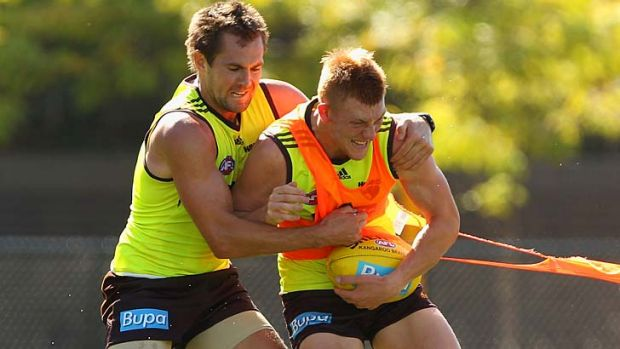 Under pressure: Luke Hodge tackles Andrew Boseley at training on Monday.
