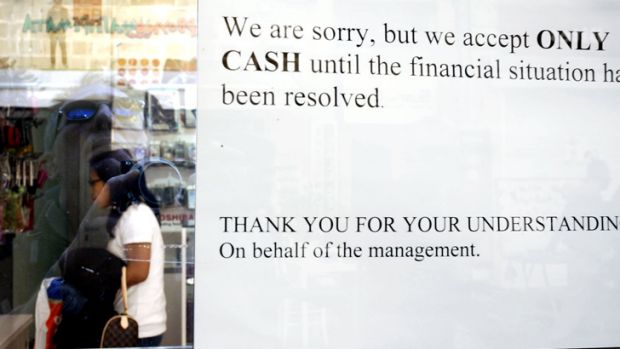 Warning signal ... A sign hangs in a window of a store in Cyprus informing shoppers that cash will only be accepted.