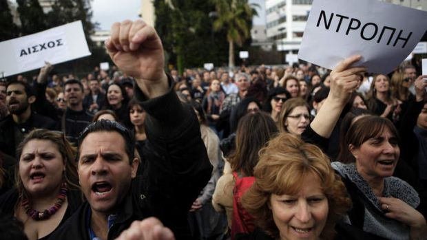 """Employees of the Bank of Cyprus hold signs reading """"shame"""" at Tuesday's protest in Nicosia."""