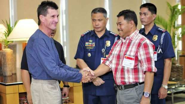 Released hostage Warren Rodwell is greeted by Philippine National Police officials and Basilan Vice-Governor Al Rashid ...