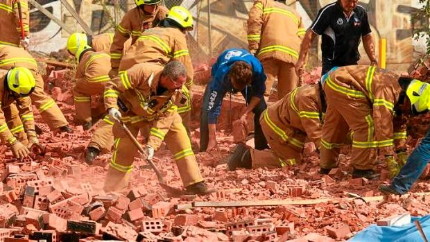 Firemen and workers frantically dig into the fallen brick wall.