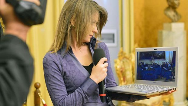 Party talks: A journalist watches the webcast.