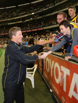 Tigers coach Damien Hardwick celebrates with supporters after their win.