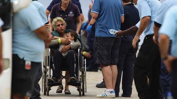 An unknown mother and child are processed by Australian officials after arriving at Flying Fish Cove on Christmas Island.