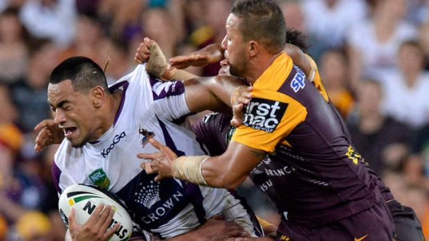 Bursting through: Storm's Junior Sa'u takes on the Brisbane line.