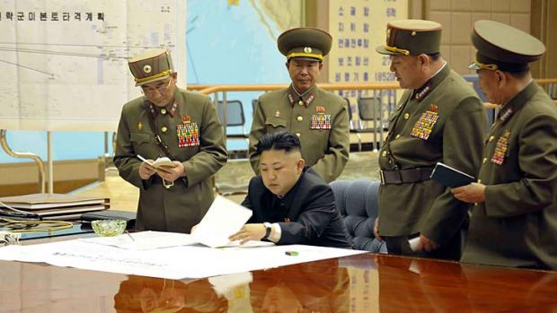 Plan of attack: Kim Jong-un with his generals on Friday. The sign on the left reads ''Strategic force's plan to hit the ...