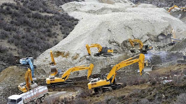 Remote: Earthmovers remove rocks at the site of the landslide.