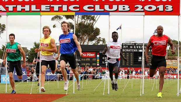 Asafa Powell (extreme right) pulls up at the end of his heat on Saturday.
