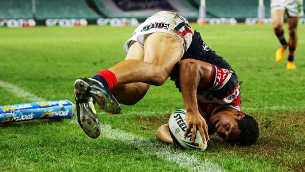Roger Tuivasa-Sheck of the Roosters dives over to score a try in the corner.