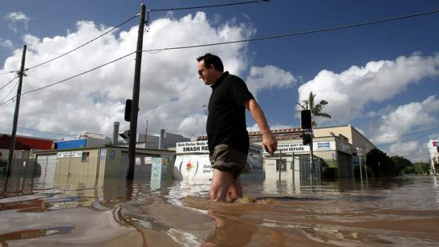 West End business owner Ross Clayton wades in knee high water on Montague Road during the 2011 flood.