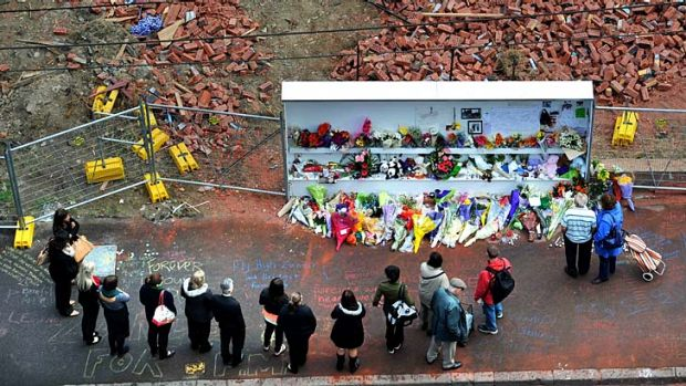 People pay their respects to the three wall victims on Tuesday.