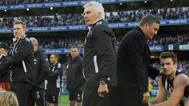 Collingwood coach Mick Malthouse, assistant coach Nathan Buckley, left and president Eddie McGuire right, watch the ...