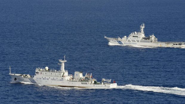 A Chinese surveillance ship  sails in front of a Japan Coast Guard vessel near disputed islands in the East China Sea.