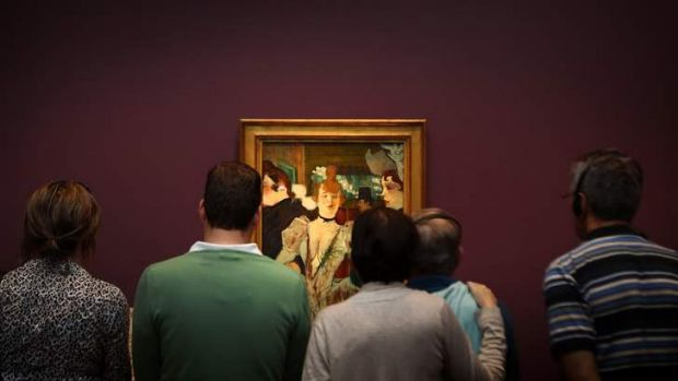 Visitors to the National Gallery of Australia look at the work La Goulue entering the Moulin Rouge during Toulouse ...