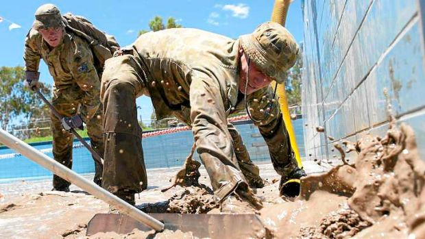 Soldiers help pump mud following the Mitchell floods in 2012.