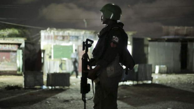 Peacekeepers: One of the Nigerian contingent to Amison, the Africa Union's force, supports Somali police on night patrol.