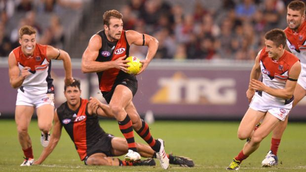 Essendon skipper Jobe Watson powers away from Melbourne's Jack Viney and Jack Grimes.