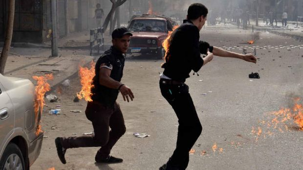 Panic on the streets ... Egyptian Coptic Christians try to put out their burning clothes after they were attacked by ...